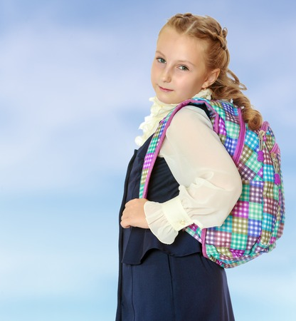 dressy: Dressy girl schoolgirl in black dress and white shirt with a knapsack on his shoulders. Close-up.On the pale blue background.