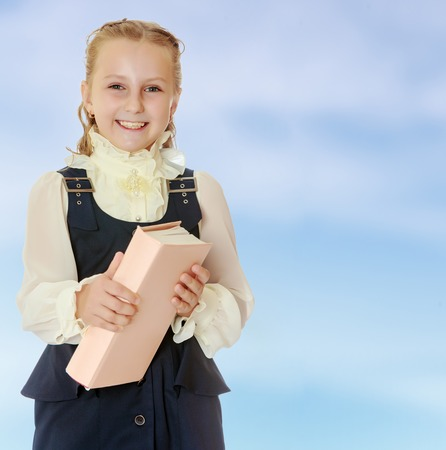 dressy: Dressy girl schoolgirl in black dress and white blouse holding a textbook and smiling cheerfully at the camera. Close-up.On the pale blue background. Stock Photo