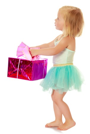 ballerina costume: Cute little girl in a ballerina costume, carrying on his outstretched hands a gift box.