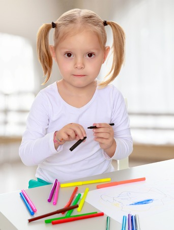 shool: The concept of pre-school education of the child among their peers . in gaming room with a large arched window.Pretty little blonde girl drawing with markers at the table.