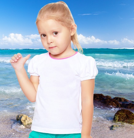 shool: The concept of family happiness and children in the summer on the sea among palm trees.Cute little blond girl in white tank top without a pattern.Girl shows thumb to the side. Stock Photo