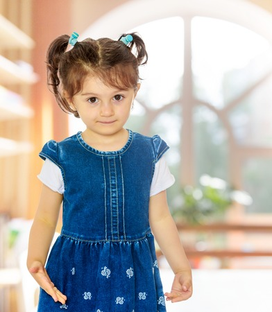 Cute little girl with short pigtails on the head, in a blue dress with short sleeves. Close-up.In a room with a large semi-circular window.