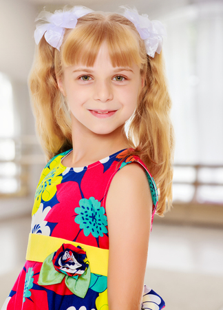 ponytails: Sweet, adorable little girl with long blonde ponytails on her head tied with white bows. Close-up.In a room with a large semi-circular window. Stock Photo