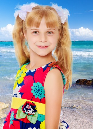 ponytails: Sweet, adorable little girl with long blonde ponytails on her head tied with white bows. Close-up.On the background of sea beach, warm sea and blue sky with clouds. Stock Photo