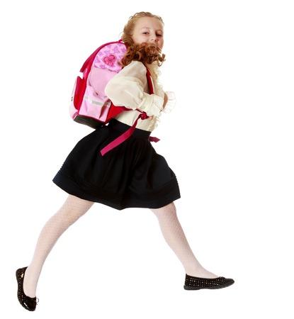 niños saliendo de la escuela: Bastante pequeña colegiala chica de blusa blanca y falda negro de prisa a la escuela. Ella salta por encima del obstacle.Isolated sobre fondo blanco. Foto de archivo
