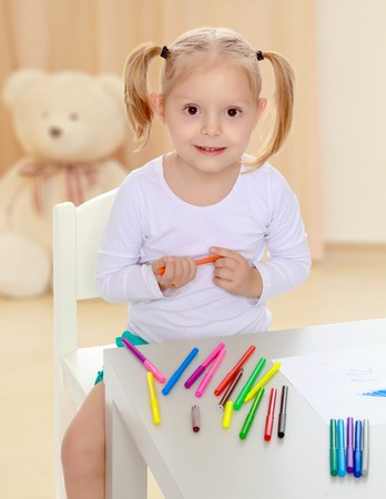 Pretty little blonde girl drawing with markers at the table.Girl holding in hands blue marker.The concept of preschool development of the child ,against a childs room where in the background a Teddy