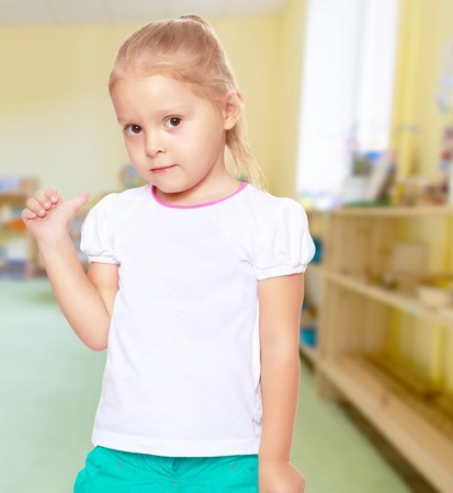 shool: The concept of pre-school education. Montessori.Cute little blond girl in white tank top without a pattern.Girl shows thumb to the side.