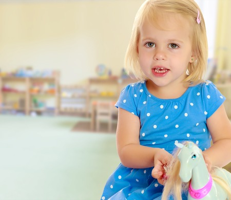 Cute little blonde girl playing with a toy horse. Girl wearing a blue dress with polka dots.On the background of the room where children live, and are on the shelves of toys. Stock Photo