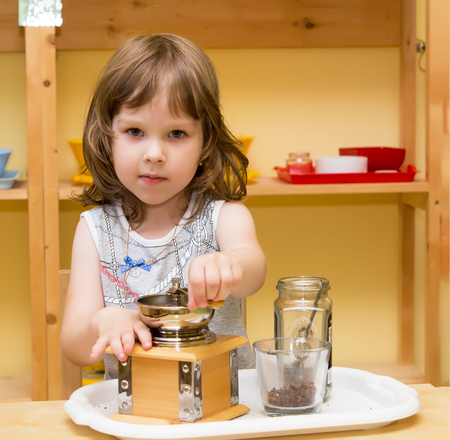Adorable little girl in the kitchen uses a hand grinder . Girl sitting at the table.Close-up. Archivio Fotografico