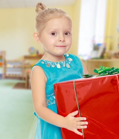 peers: The concept of pre-school education of the child among their peers . on the background of the playroom with shelves for toys. Montessori.Caucasian little girl in a blue dress