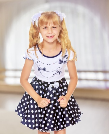 Beautiful little blonde girl in polka dot dress,the girl upset. Close-up.In a room with a large semi-circular window.
