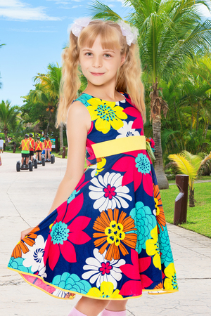 Beautiful little girl with long blonde ponytails on the head and white bows in bright summer dress keeps the dress over the edge.On the background of the road, palm trees and blue sky with clouds.
