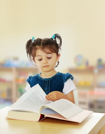 Pretty little girl in blue denim dress reading a book sitting at the table.In the Montessori room the childrens garden where there are shelves with toys and material. Stock Photo