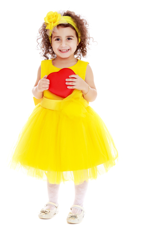 Adorable little girl in bright yellow elegant dress. Close to her heart.Isolated on white background.