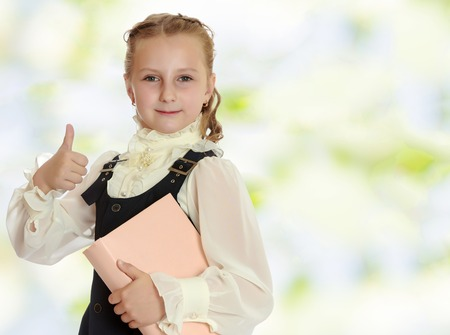 dressy: Dressy girl schoolgirl in black dress and white blouse holding a textbook and shows thumb. Gesture all right. Close-up.Summer white green blurred background. Stock Photo