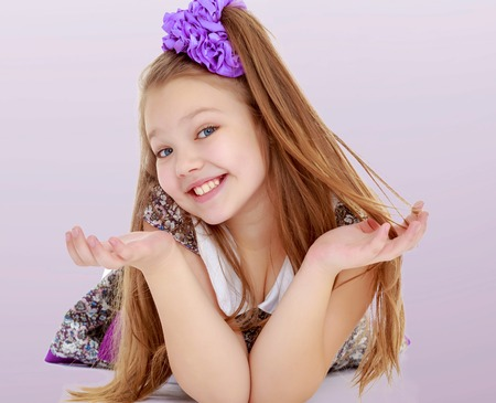 sweetly: Happy little girl with a big purple bow on her head lying on the floor. Girl throws hands and smiling sweetly at the camera.Gradient purple background.