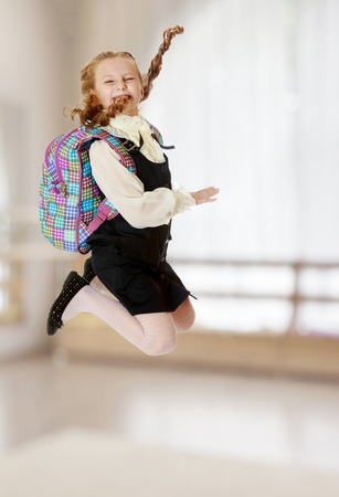 Happy girl schoolgirl in black dress and white shirt and a knapsack on his shoulders. She jumps, hands up. Turning sideways to the camera.In a room with a large semi-circular window.