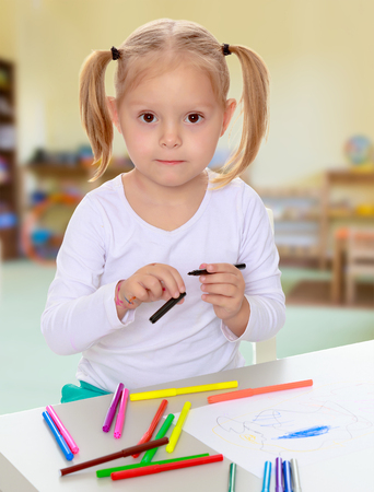 shool: Pretty little blonde girl drawing with markers at the table.Girl holding in hands blue marker.The concept of pre-school education of the child among their peers . Stock Photo