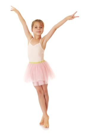 Adorable little girl in pink dress ballerina standing on tiptoe with her arms out to the sides.Isolated on white.