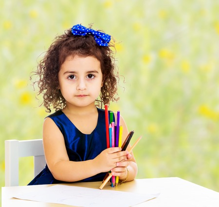 Cute little girl in blue dress, holds a lot of pencils . She paints at a table in a Montessori kindergarten.Bright,floral yellow-green blurred background.