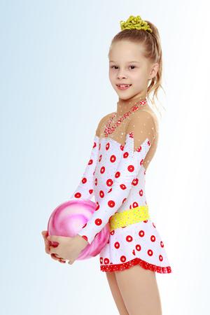 Gymnast tut Übungen mit einem Ball Standard-Bild - 74480076