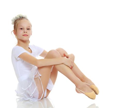 女の子の体操選手が床に座ってポーズします。