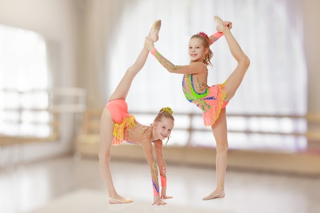 Two girls gymnast sitting on splits. Stock Photo