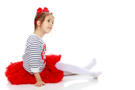 Little girl in a red skirt and bow on her head. Stock Photo