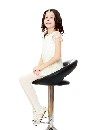 Little girl sitting in a swivel chair. Stock Photo