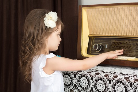 Little girl listens to old radio. Stock Photo