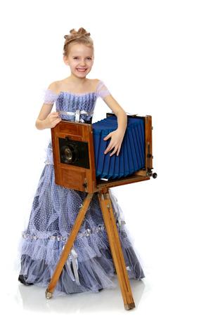 Little girl posing near the old camera.