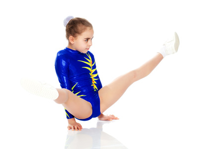 A girl gymnast performs exercises on the floor. Stock Photo