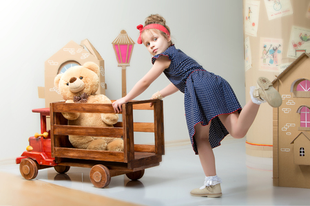 Little girl playing with a big wooden car.