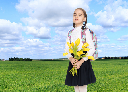 sho: A schoolgirl with a bouquet of flowers and a backpack on her sho Stock Photo