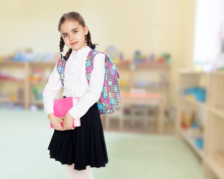 The girl is a schoolgirl with a book in her hands.