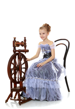 Little girl sitting at a spinning wheel.