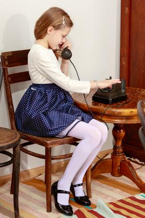 Meisje praten over oude telefoon. Stockfoto