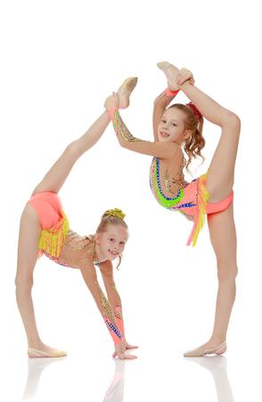 Two girls gymnast sitting on splits. Фото со стока