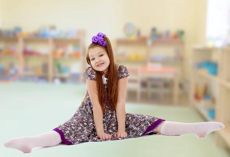 Beautiful little girl sitting on twine
