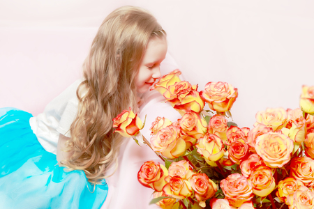 in full bloom: A beautiful little girl with long, light, curly hair, in a blue