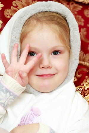 The little girl is waving her hand.