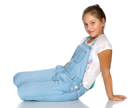 A teenage girl is sitting on the floor. Stock fotó