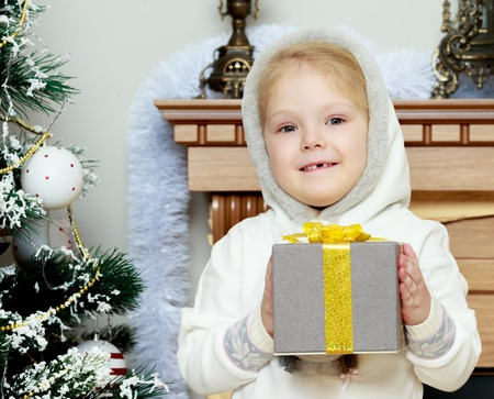 victorian christmas: Little girl with a gift in her hands.