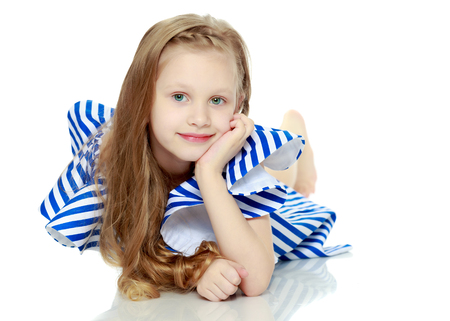 Adorable little blond girl in very short summer striped dress.Sh