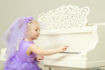 girl is playing on a white grand piano.