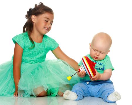 Una niña con su hermano jugando Foto de archivo