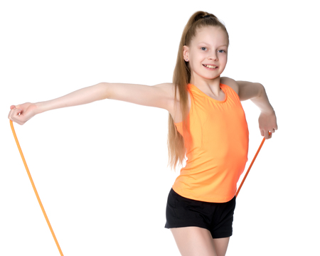 A girl gymnast performs exercises with a skipping rope. Standard-Bild - 90250159