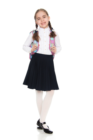 Beautiful schoolgirl with a backpack behind her shoulders. Stock Photo