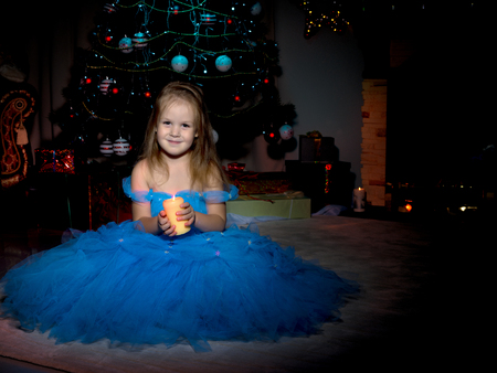A little girl is holding a candle.
