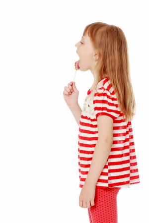 小さな女の子が棒にキャンディーを舐める。 写真素材 - 91600001